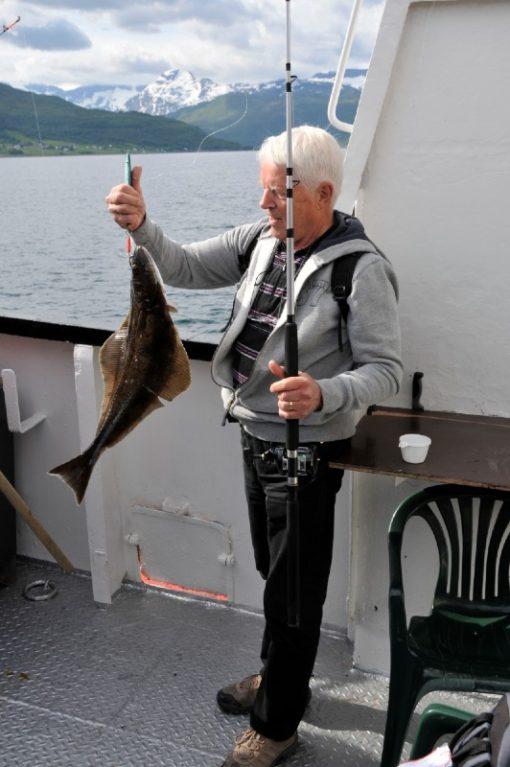 Man håller upp fångsten efter fiske i fjällsjö