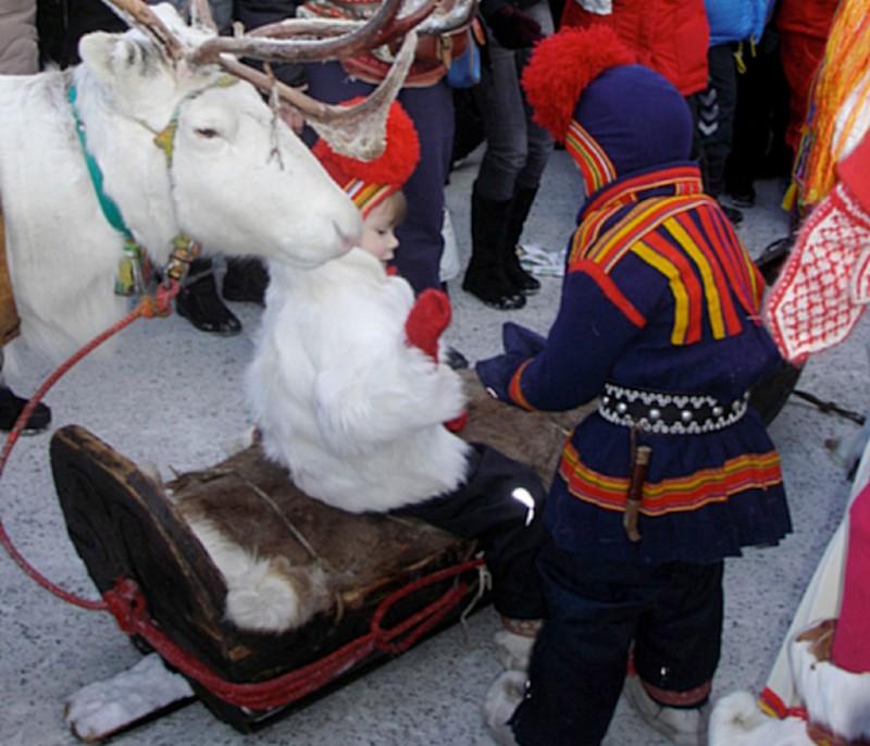 Flicka sitter i släde på Jokkmokks Marknad